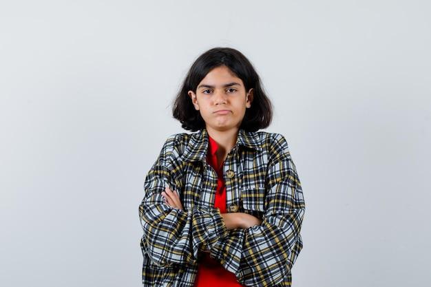 Klein meisje staat met gekruiste armen in shirt, jas en kijkt beledigd. vooraanzicht.