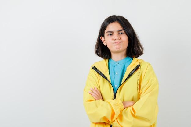 Klein meisje staat met gekruiste armen terwijl ze wangen in shirt, jas blaast en er zelfverzekerd uitziet, vooraanzicht.