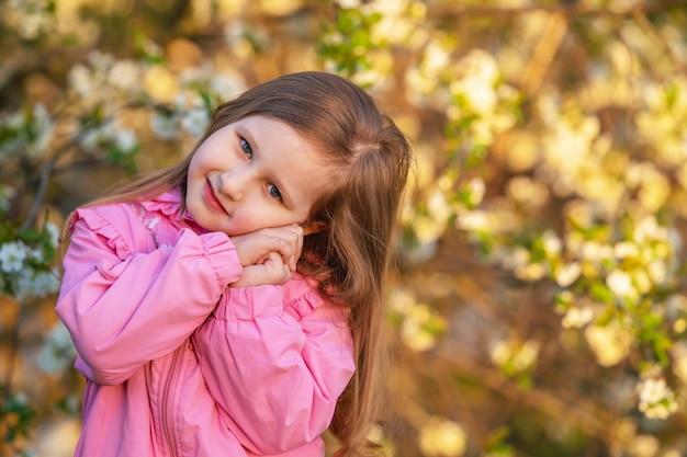 Klein meisje staat met haar handen gevouwen onder haar wang