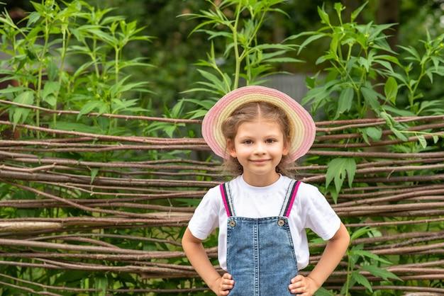 Klein meisje staat tegen een rieten hek.