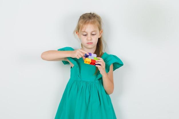 Klein meisje stapelen veelkleurige speelgoed bakstenen in groene jurk