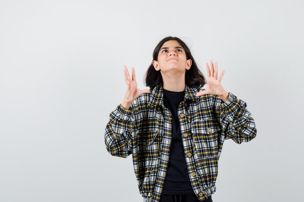 Klein meisje steekt handen op agressieve manier op in t-shirt, jas en kijkt woedend. vooraanzicht.