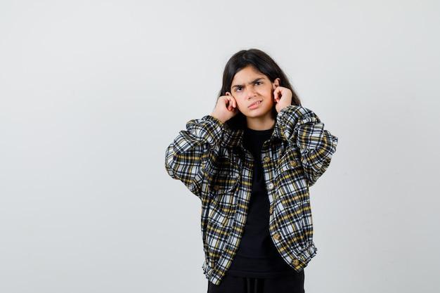 Klein meisje stopt oren met vingers in t-shirt, jas en kijkt geïrriteerd. vooraanzicht.