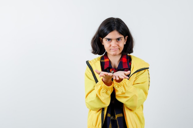 Klein meisje strekt zich uit tot komvormige handen in geruit overhemd, jasje en ziet er zelfverzekerd uit. vooraanzicht.