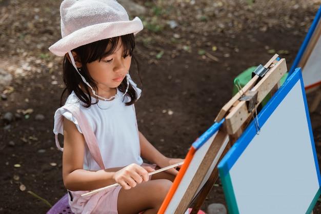 Klein meisje tekenen in het park