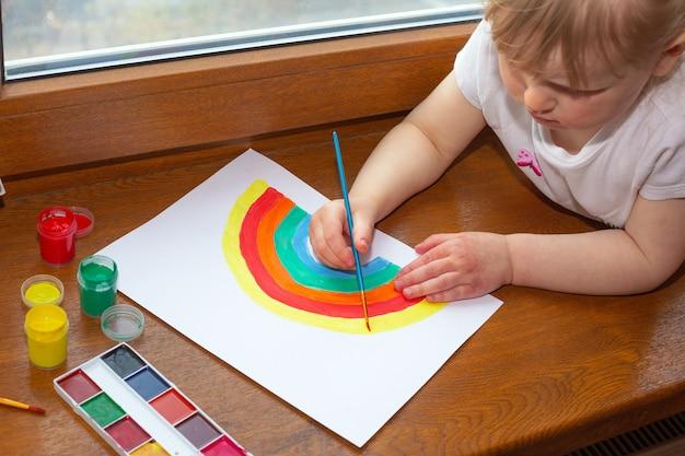 Klein meisje tekening regenboog. teken van hoop tijdens een uitbraak van het coronavirus.