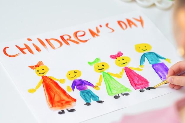 Klein meisje tekent de kinderen met woorden children's day voor de vakantie happy children's day.