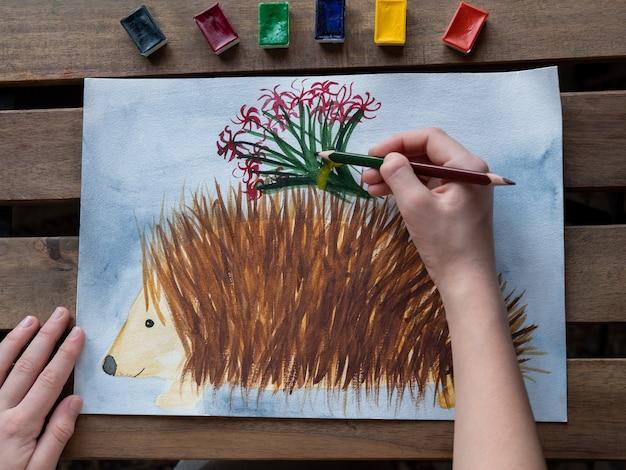 Klein meisje tekent een egel met aquarellen en potloden