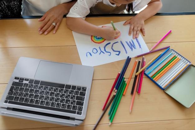 Klein meisje tekent een ik mis je-bericht op papier voor een videogesprek