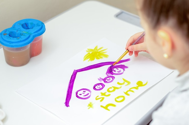 Klein meisje tekent familie onder een dak met woorden stay home door aquarellen op wit vel papier. blijf thuis-concept.