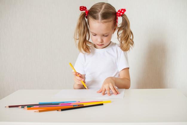 Klein meisje tekent met kleurpotloden. thuisonderwijs