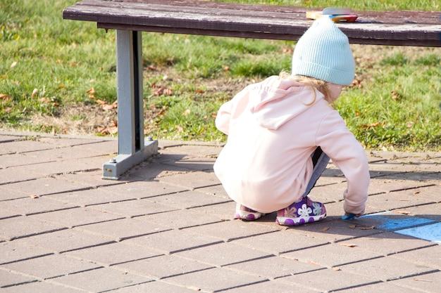 Klein meisje tekent met krijt. het park. herfst.