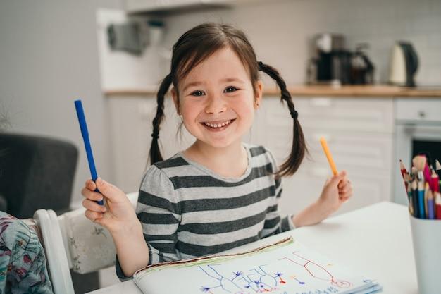 Klein meisje tekent thuis een foto. meisje met twee vlechten die thuis online studeren. getalenteerd meisje dat een foto schildert.