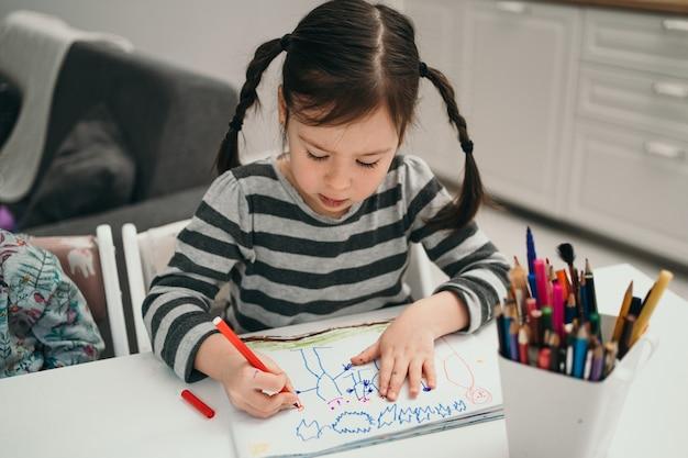 Klein meisje tekent thuis een foto. meisje met twee vlechten die thuis online studeren. getalenteerd meisje dat een foto schildert