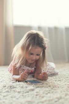Klein meisje thuis met smartphone
