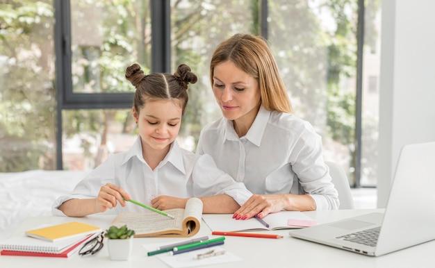 Klein meisje thuis studeren met haar leraar