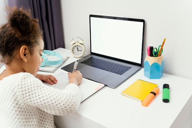 Klein meisje thuis tijdens online school met behulp van laptop