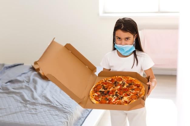 Klein meisje thuis tijdens quarantaine en pizza eten.