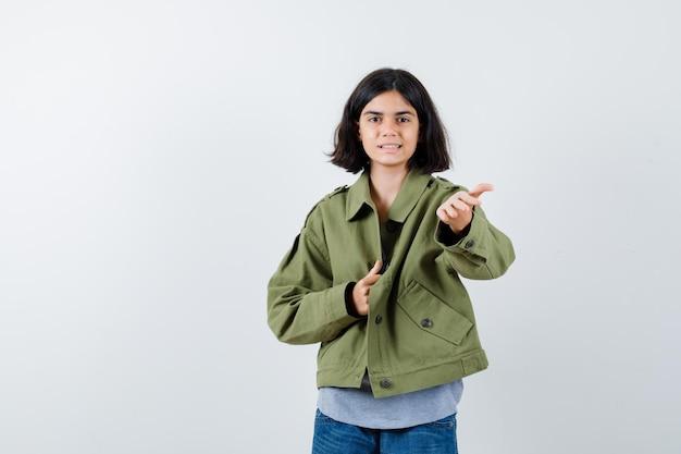 Klein meisje toont gebaar in jas, t-shirt, spijkerbroek en ziet er mooi uit, vooraanzicht.