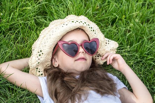 Klein meisje tot in het gras. zomertijd en zonnige dag
