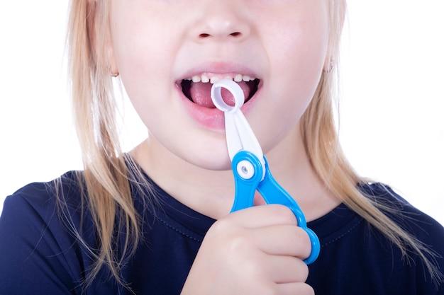 Klein meisje trekt een tand met speelgoed tang