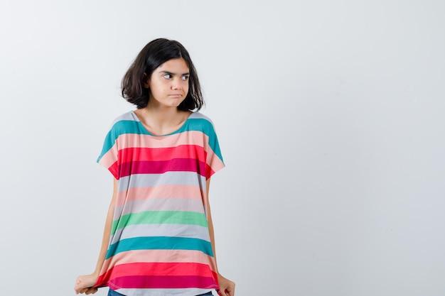 Klein meisje trekt haar t-shirt in t-shirt en kijkt beschaamd. vooraanzicht.