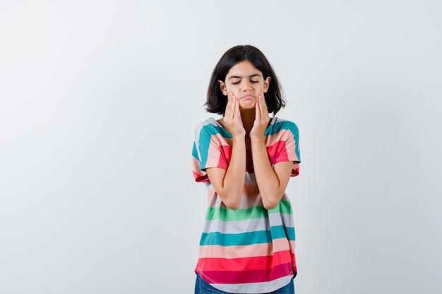 Klein meisje trekt huid op haar wangen in t-shirt en kijkt boos, vooraanzicht.
