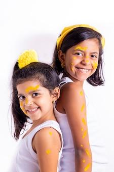 Klein meisje twee, met haar gezicht geschilderd om de gele dag te vieren