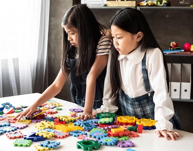 Klein meisje twee spelen samen plasticine, met geïnteresseerd gevoel, thuis studio, lens flare effect, wazig licht rond