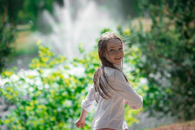Klein meisje veel plezier in de buitenfontein op een warme dag