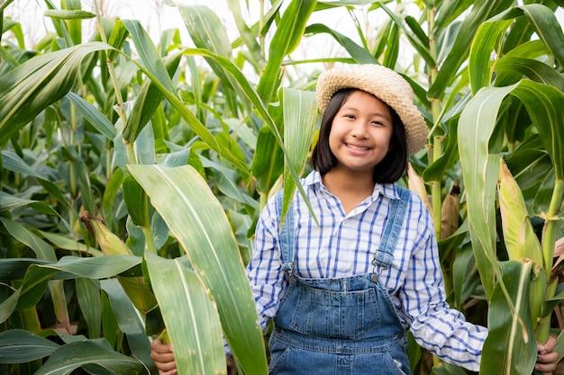 Klein meisje verborgen en zie product tracking in maïsveld. ze heeft een frisse glimlach en geluk in de avond. maïsproducten worden gebruikt om voedsel voor mens en dier te produceren. landbouw concept. warm voor