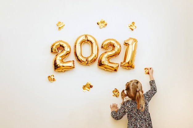 Klein meisje versiert de muur van het huis met gouden cijfers 2021. het huis voorbereiden op kerstmis