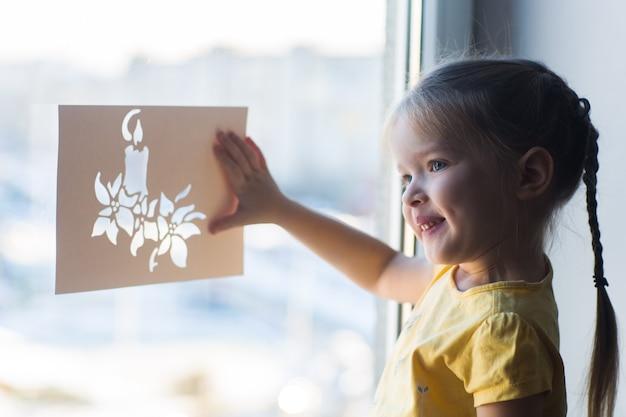 Klein meisje versiert het raam voor het nieuwe jaar en kerstmis
