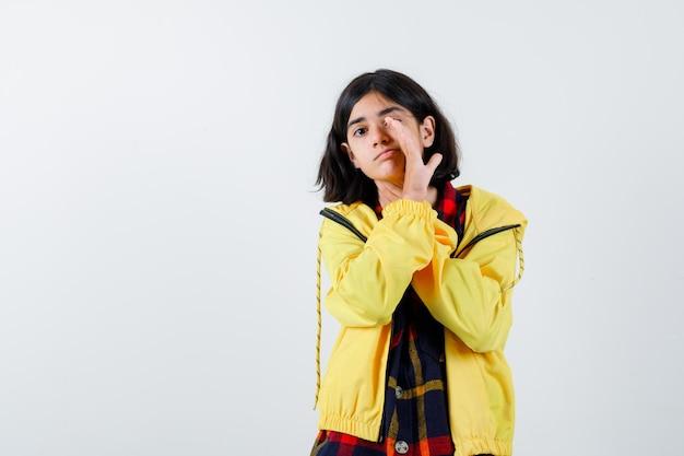 Klein meisje vertelt geheim achter hand in geruit hemd, jasje en kijkt voorzichtig. vooraanzicht.