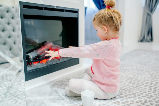 Klein meisje verwarmt haar handen bij de open haard in een gezellige kamer thuis
