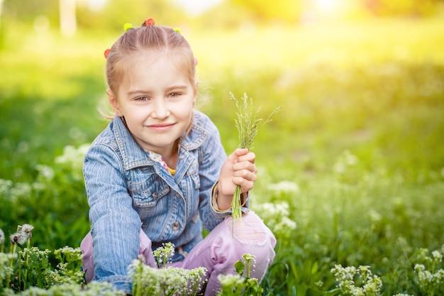 Klein meisje verzamelt bloemen