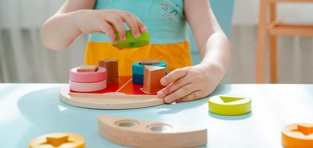 Klein meisje verzamelt houten veelkleurige sorter veilig natuurlijk houten kinderspeelgoed