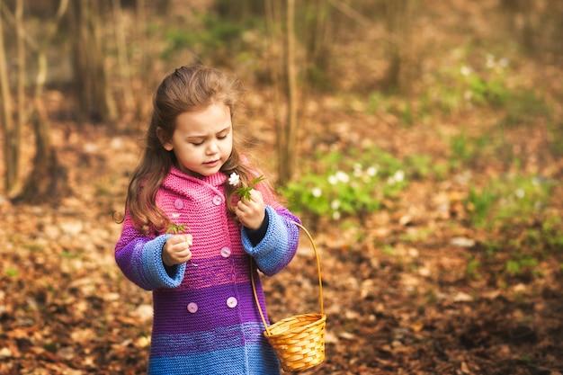 Klein meisje verzamelt sneeuwklokje bloemen in het bos
