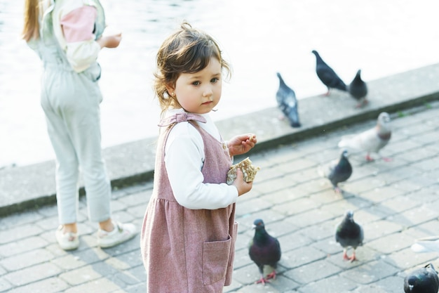Klein meisje vogels voeren in een stadspark