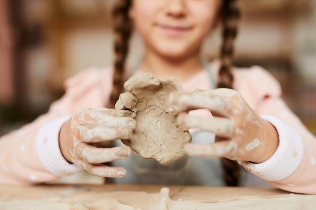 Klein meisje vormgeven van klei