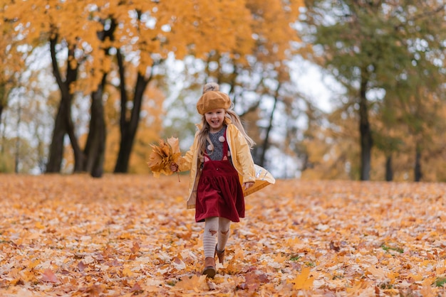 Klein meisje wandelen in het park met blad herfst natuurtuin