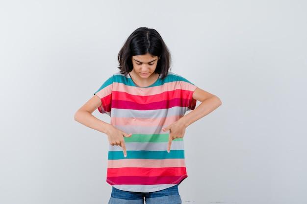 Klein meisje wijst naar beneden met wijsvingers in t-shirt, spijkerbroek en kijkt gefocust, vooraanzicht.
