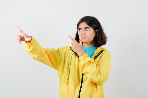 Klein meisje wijst naar de linkerbovenhoek in shirt, jas en ziet er zelfverzekerd uit. vooraanzicht.