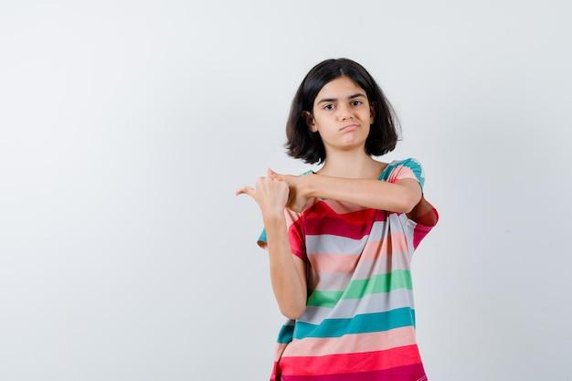 Klein meisje wijst naar links in t-shirt, spijkerbroek en ziet er ontevreden uit. vooraanzicht.