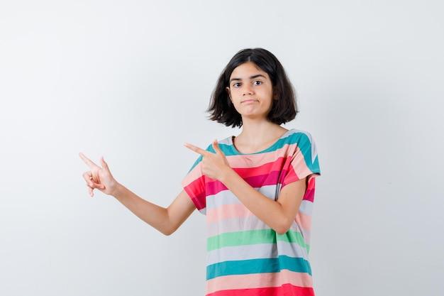 Klein meisje wijst naar links met wijsvingers in t-shirt, spijkerbroek en ziet er serieus uit. vooraanzicht.