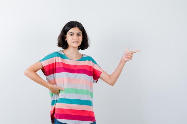 Klein meisje wijst naar rechts met wijsvinger terwijl ze de hand op de taille houdt in een t-shirt, jeans en er gelukkig uitziet. vooraanzicht.