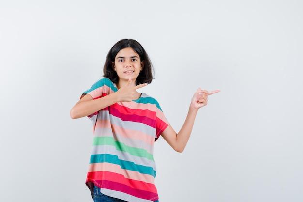 Klein meisje wijst naar rechts met wijsvingers in t-shirt, jeans en ziet er gelukkig uit. vooraanzicht.