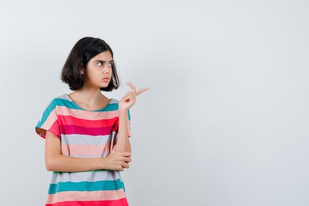 Klein meisje wijst naar rechts terwijl ze de hand op de elleboog houdt in een t-shirt, spijkerbroek en er gefocust uitziet, vooraanzicht.
