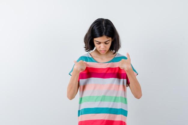 Klein meisje wijst naar zichzelf in t-shirt, spijkerbroek en kijkt serieus. vooraanzicht.