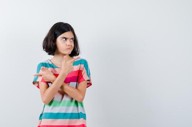 Klein meisje wijst tegenovergestelde richtingen in t-shirt, jeans en kijkt serieus, vooraanzicht.
